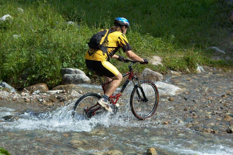 De fietser en de kreek van de berg stock afbeelding