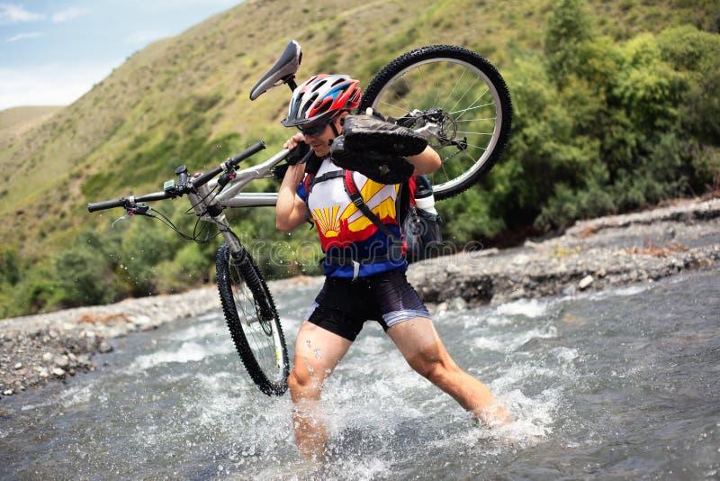 De fietser gaat over bergrivier royalty-vrije stock fotografie