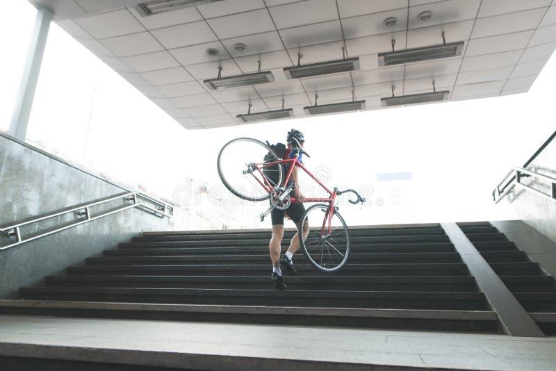 De fietser in sporten draagt uit metro met een fiets in zijn handen De mens komt uit een ondergrondse passage stock afbeelding