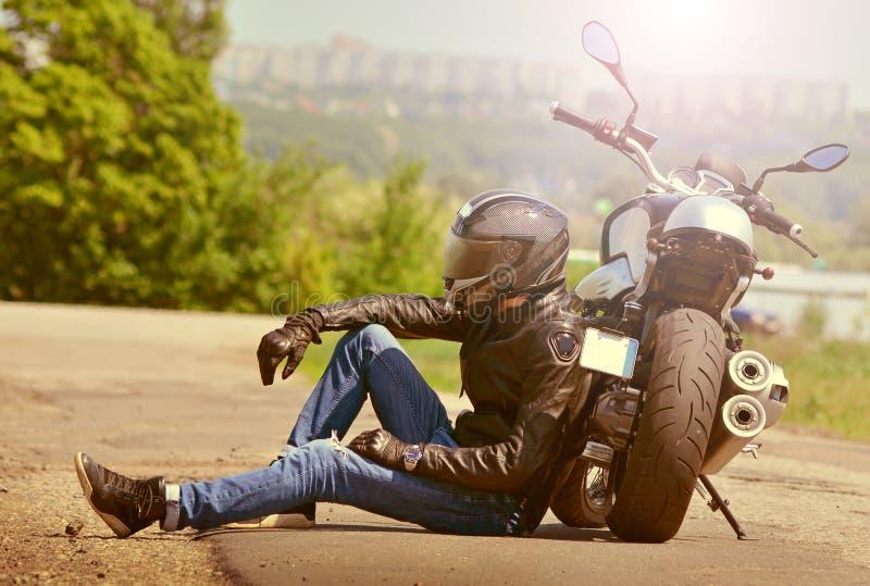 De fietser in uitrusting zit naast motorfiets op asfalt De motorrijder rust dichtbij de motor gestemd royalty-vrije stock afbeelding