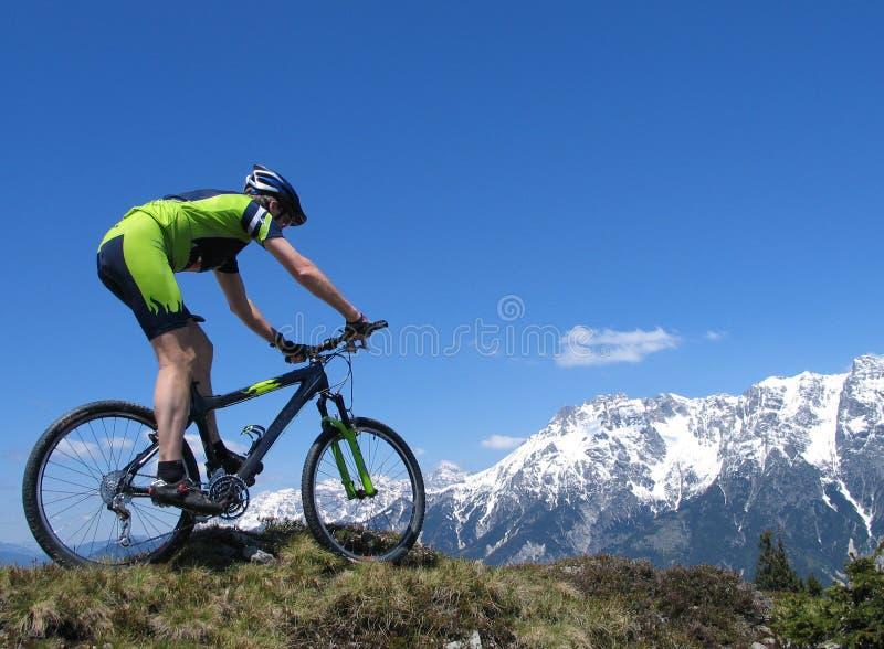 De fietser van de berg tegen achtergrond van sneeuwbergen royalty-vrije stock foto's