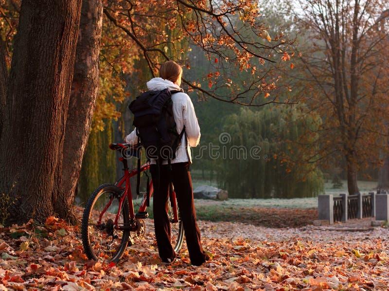 De fietser van de vrouw met fiets en rugzak in park stock fotografie