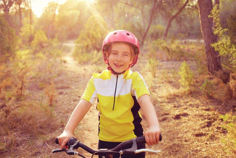 De fietser van het jong geitjemeisje in bergfiets MTB stock afbeelding