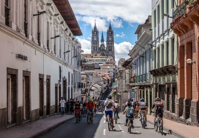 De fietsers en de voetgangers op een zondag sloten straat van Quito en Basiliek del Voto Nacional - Quito, Ecuador royalty-vrije stock foto