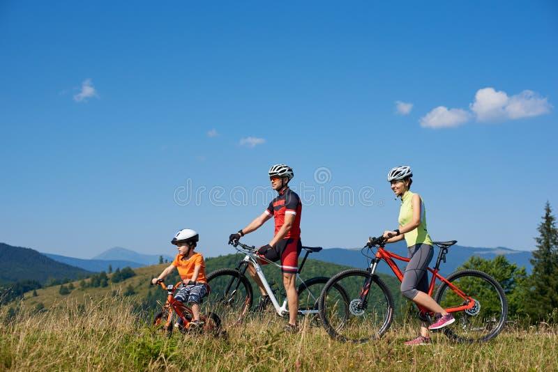 De fietsers, de moeder, de vader en het kind die van de familietoerist met fietsen op de bovenkant van grasrijke heuvel rusten stock foto