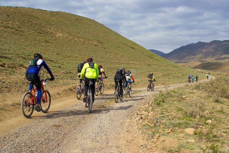 De fietsers van de berg groeperen het rennen in woestijn royalty-vrije stock fotografie