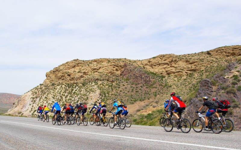 De fietsers van de berg groeperen zich op weg stock afbeeldingen