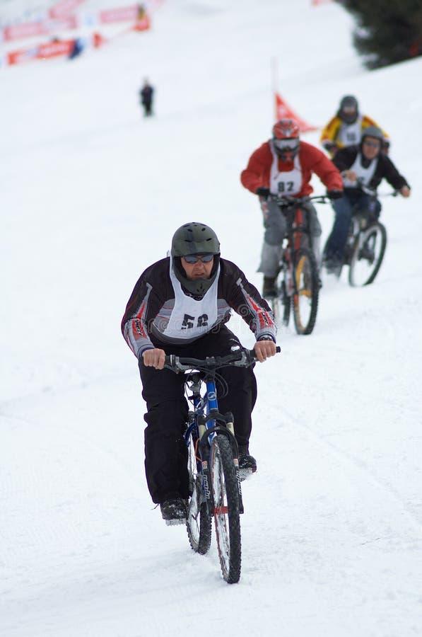De fietsers van de sneeuw op ras stock fotografie