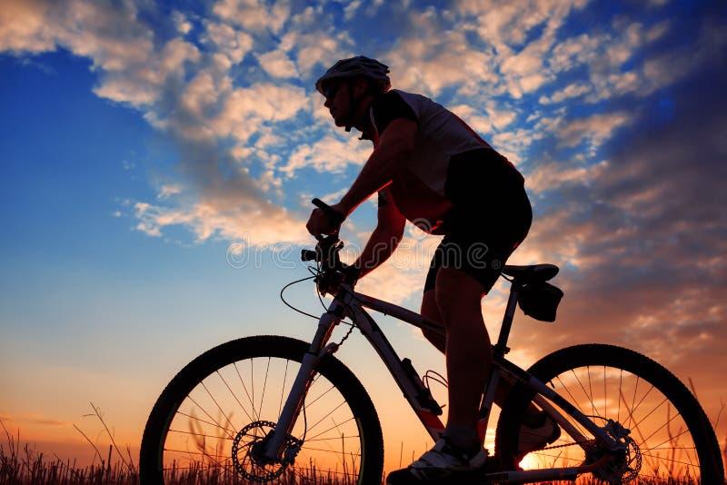 De fietsersilhouet van de berg in zonsopgang stock fotografie