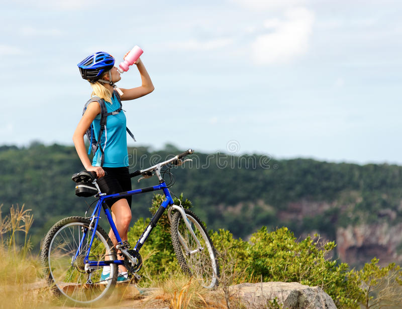 De fietsmeisje van de berg het drinken stock afbeeldingen