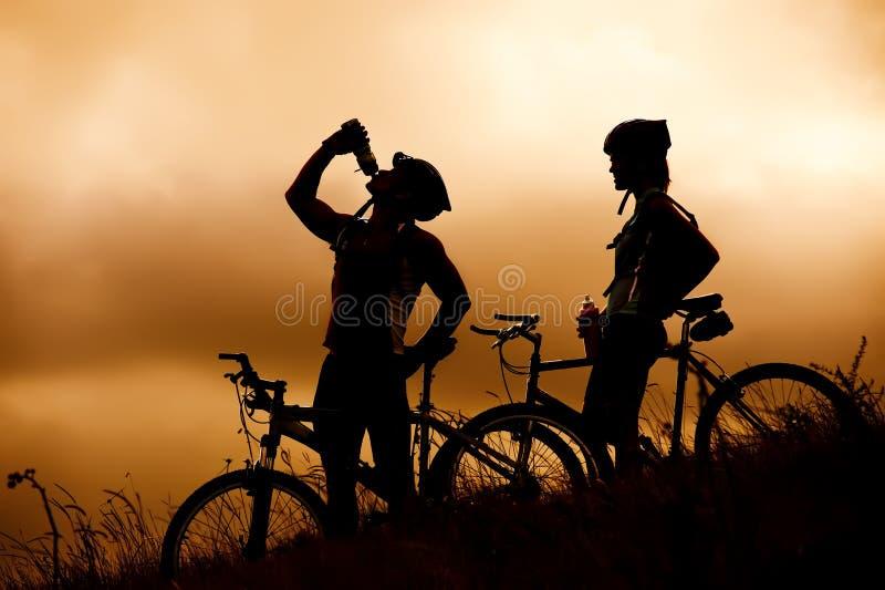 De fietspaar van de berg het drinken in silhouet royalty-vrije stock foto's