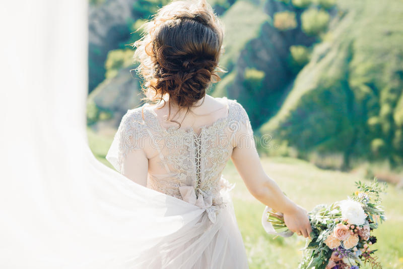 De fijne fotografie van het kunsthuwelijk Mooie bruid met boeket en kleding met trein in aard stock fotografie