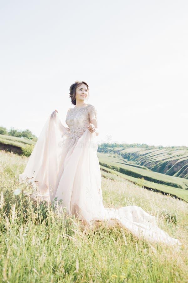 De fijne fotografie van het kunsthuwelijk Mooie bruid met boeket en kleding met trein in aard royalty-vrije stock afbeelding