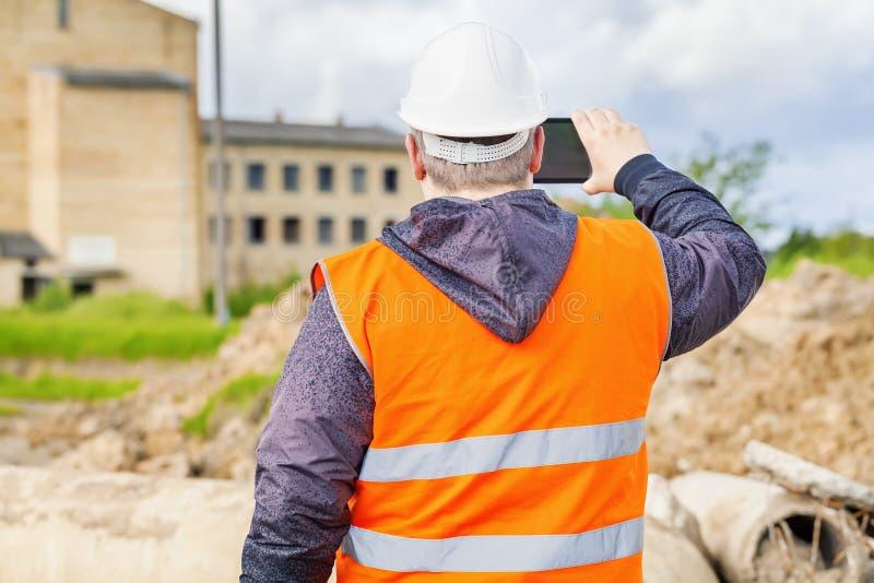 De film van de bouwinspecteur met tabletpc die dichtbij bouwen stock afbeeldingen