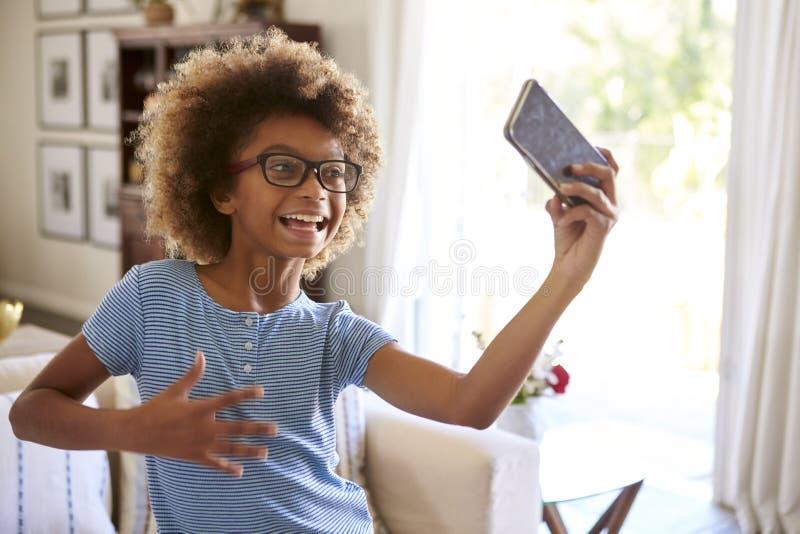 De film van het pre-tienermeisje zelf het zingen gebruiken sociale media app op haar smartphone, sluit omhoog royalty-vrije stock afbeelding