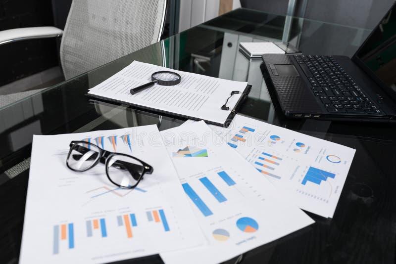 De financiële documenten met vergrootglas en verzekering liggen op zwarte lijst in bureauclose-up stock foto's