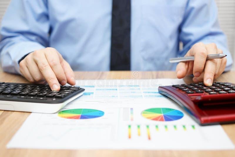 De financiële specialist werkt met calculator en computer aan royalty-vrije stock foto