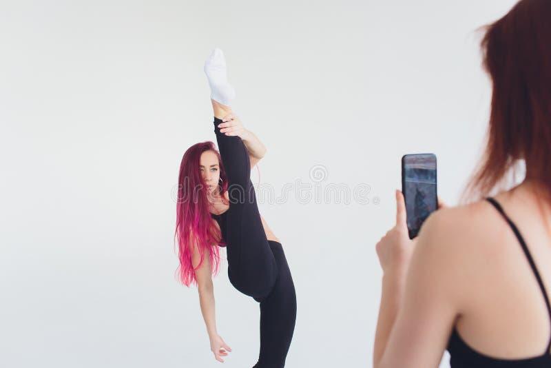 De fitness van de meisjessport de mat van de gymnastieksmartphone van yoga pilates carimat oefeningen carimat oefent op een beige royalty-vrije stock afbeeldingen