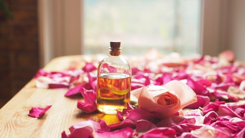 De fles aromaolie met roze nam en rozenbloemblaadjes op houten oppervlakte, geselecteerde nadruk toe royalty-vrije stock fotografie