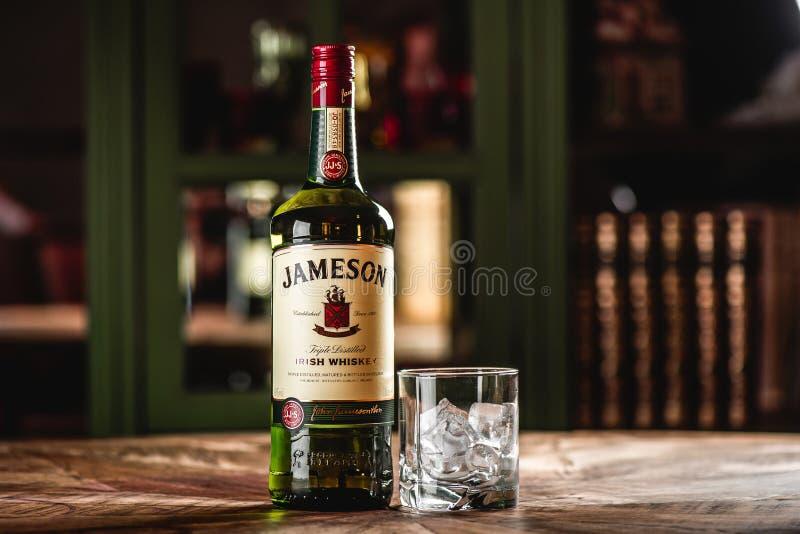 De fles en het glas van de Jamesonwhisky met ijsblokjes op houten lijst royalty-vrije stock foto