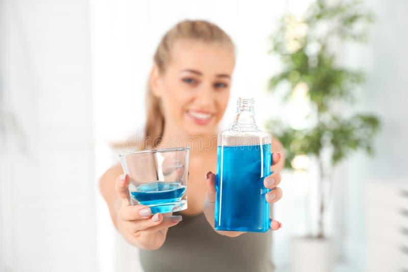 De fles en het glas van de vrouwenholding met mondspoeling stock afbeeldingen