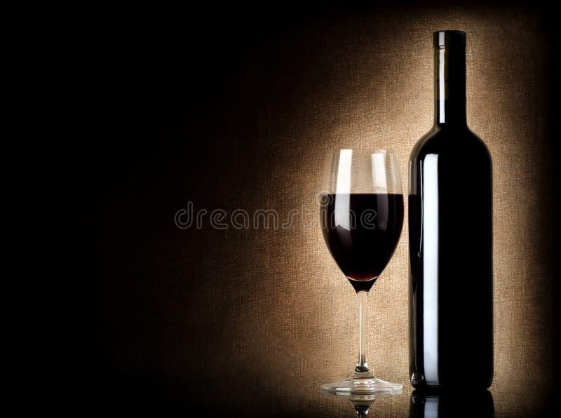 De fles en het wijnglas van de wijn op een oude achtergrond stock afbeelding
