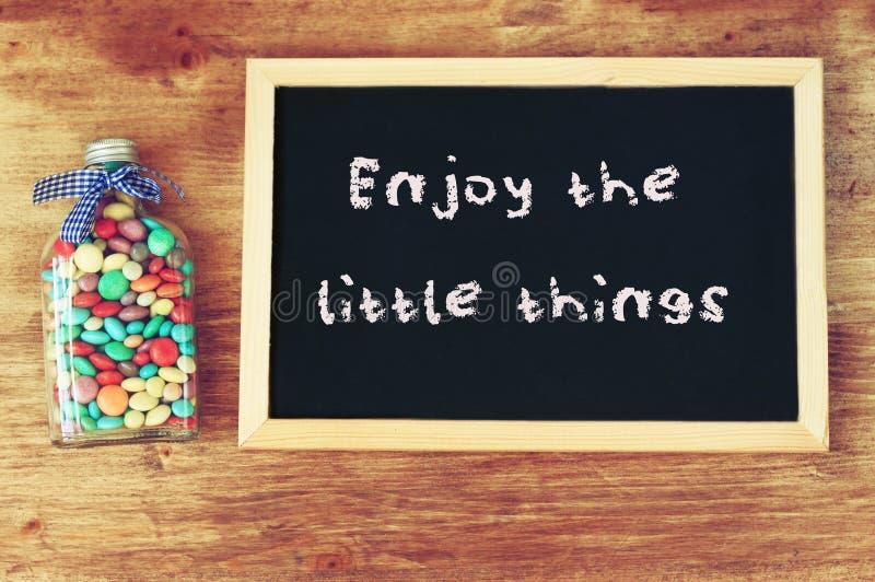 De fles met suikergoed wordt gevuld en het bord met de uitdrukking genieten van de kleine dingen dat stock afbeeldingen