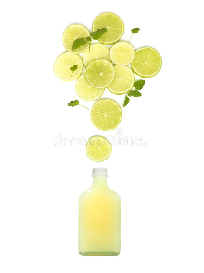 De fles met vers citroensap bevindt zich onder vele kalkplakken en muntbladeren op witte achtergrond royalty-vrije stock afbeelding