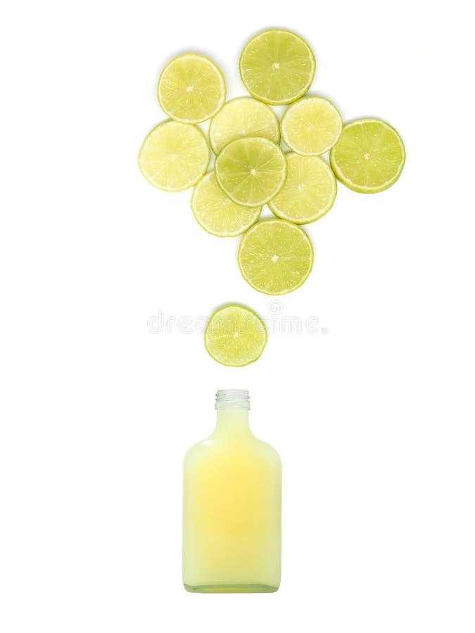 De fles met vers citroensap bevindt zich onder vele kalkplakken op witte achtergrond stock foto's