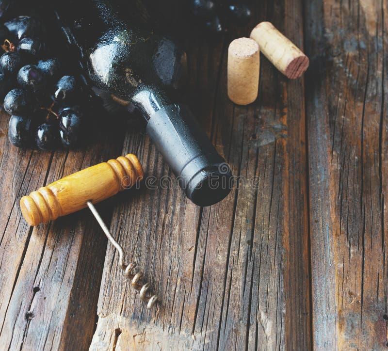 De fles rode wijn met verse druif en bos van kurkt op houten lijst stock foto