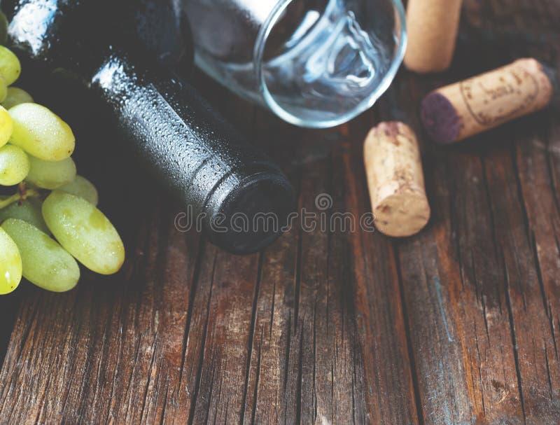 De fles rode wijn met verse druif en bos van kurkt op houten lijst stock afbeelding