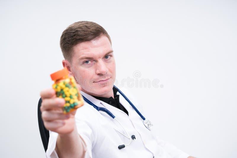 De fles van de artsenholding van pillen stock foto