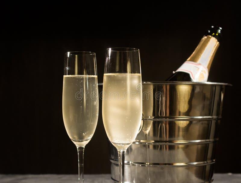 De fles van Champagne in koeler en twee champagneglazen stock afbeeldingen