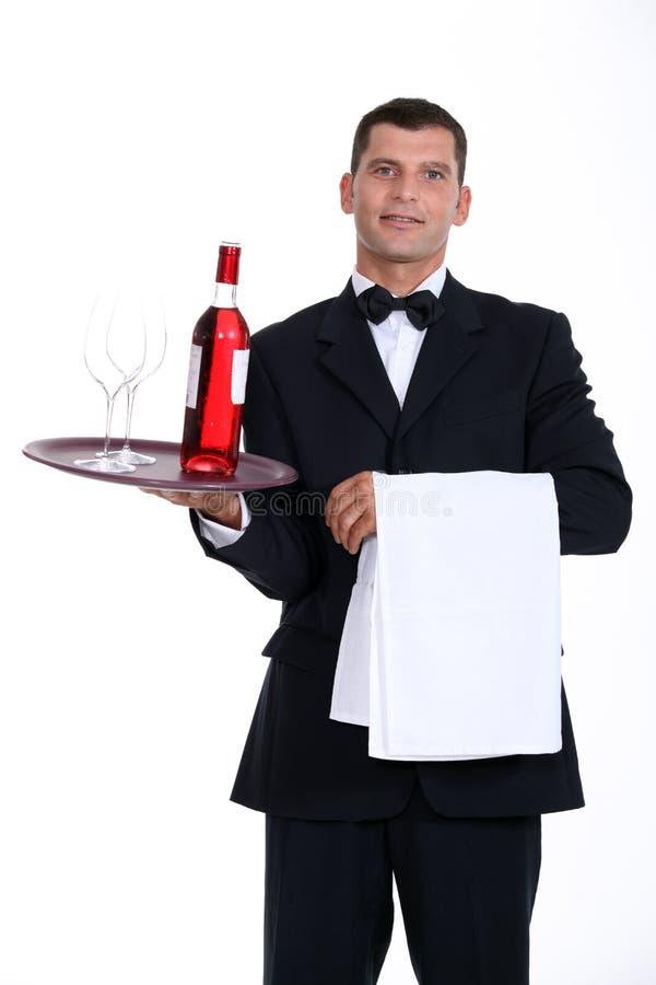 De fles van de kelnersholding wijn royalty-vrije stock afbeeldingen
