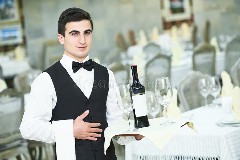 De fles van de kelnersholding wijn en glazen royalty-vrije stock afbeelding