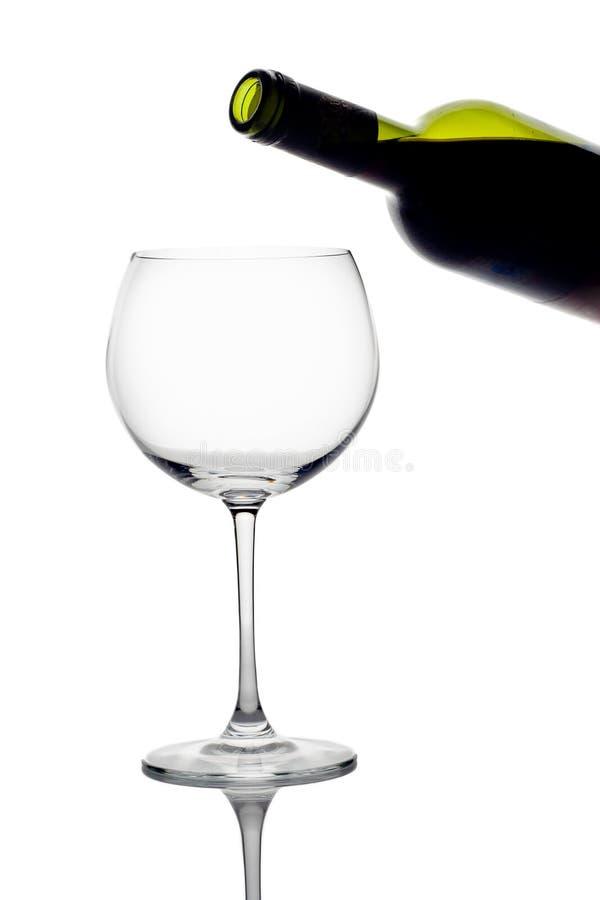 De fles van de wijn en een leeg glas stock fotografie