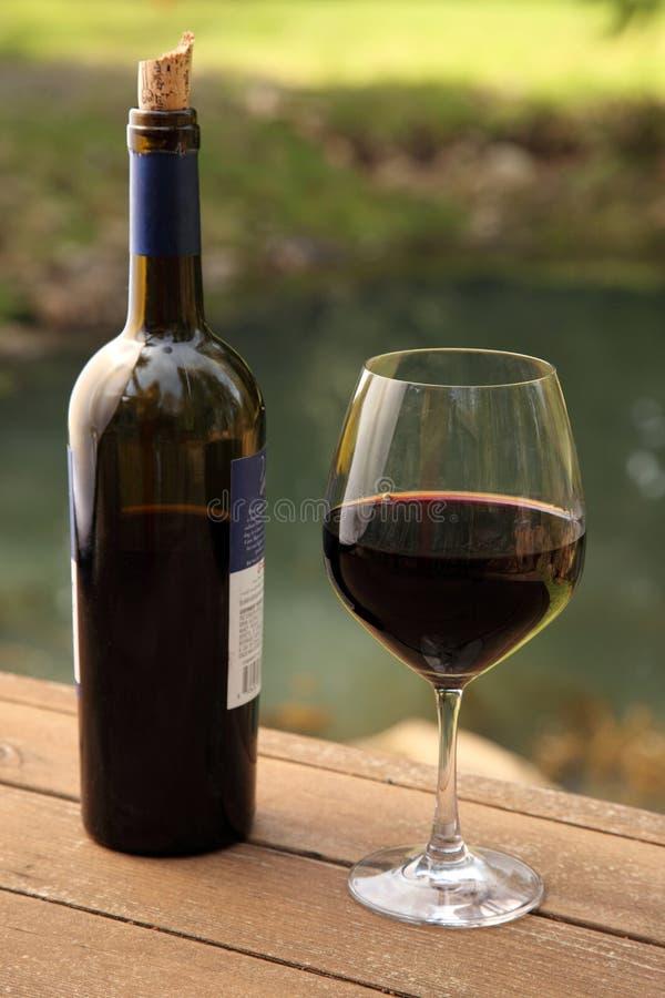 De fles van de wijn en glas van rode vino stock foto's