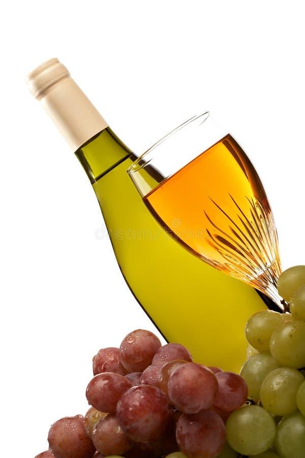 De fles van de wijn en glas wijn met geïsoleerdeàdruiven stock afbeelding
