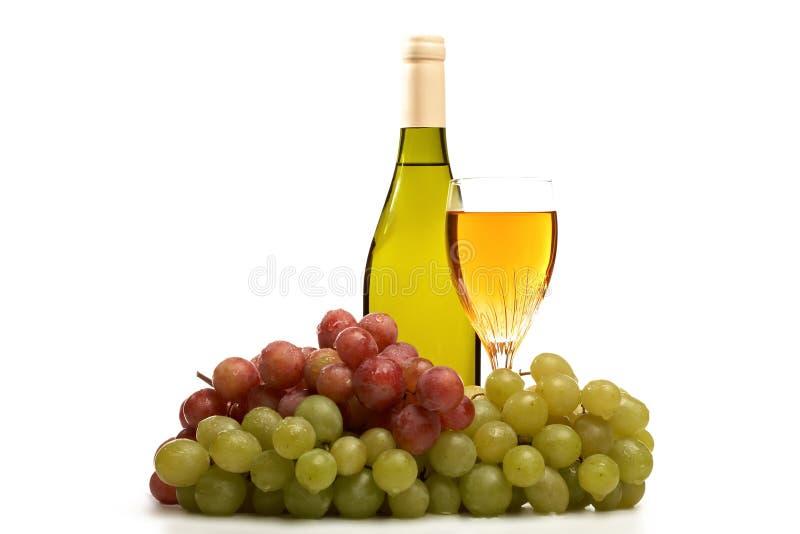 De fles van de wijn en glas wijn met geïsoleerde druiven royalty-vrije stock foto's