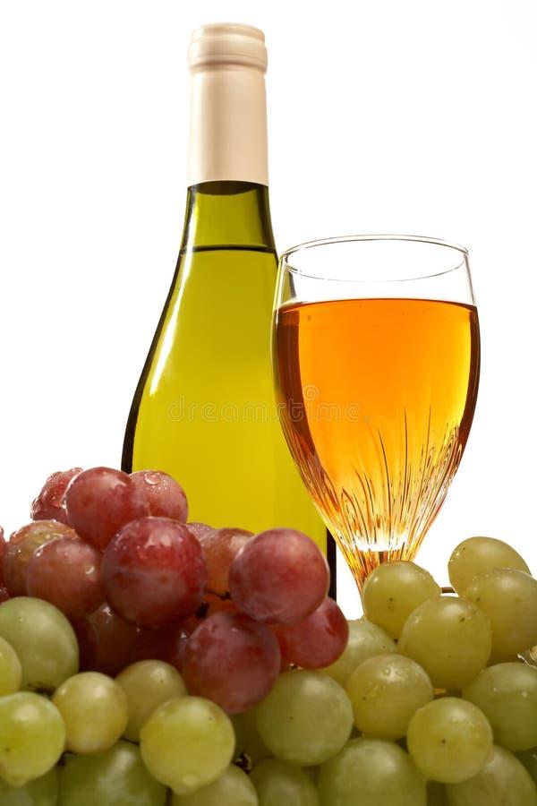 De fles van de wijn en glas wijn met geïsoleerdeg druiven stock foto's