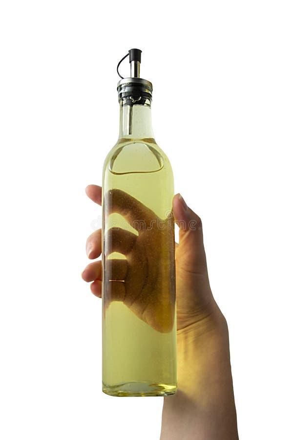 De fles van de handholding met olie op wit Kokende ingrediënten Geïsoleerde olie stock afbeelding