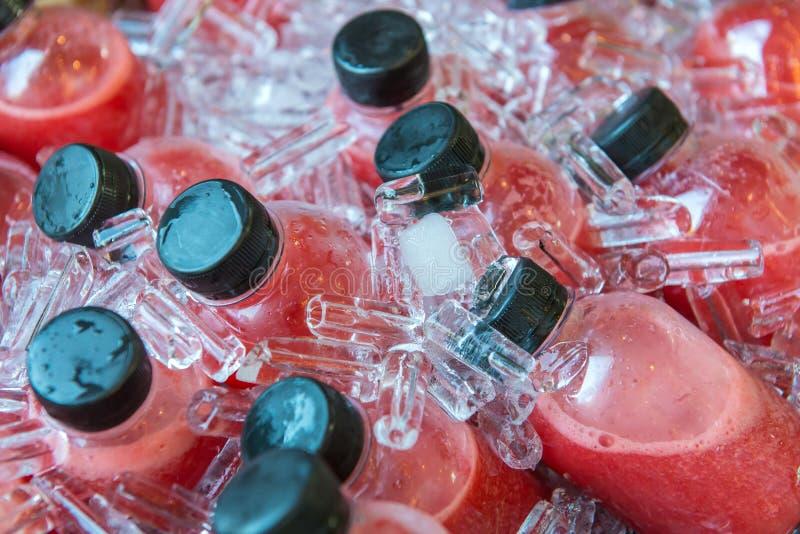 De fles van het aardbeisap ijskoud in de koelbox royalty-vrije stock afbeelding