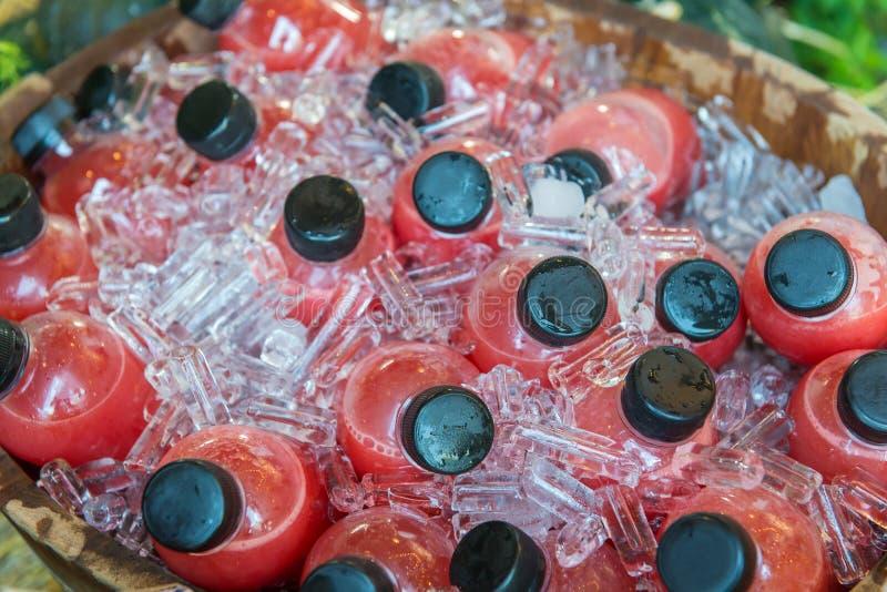 De fles van het aardbeisap ijskoud in de koelbox stock fotografie