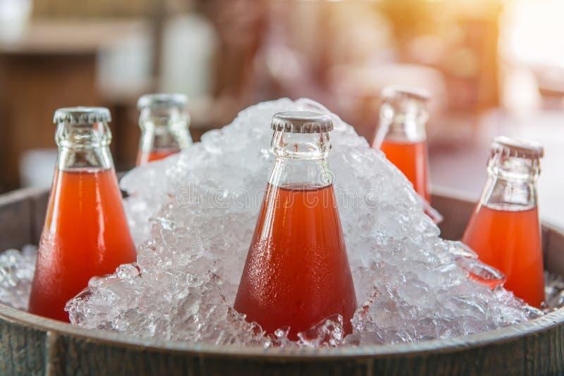 De fles van het aardbeisap ijskoud in de koelbox stock foto's
