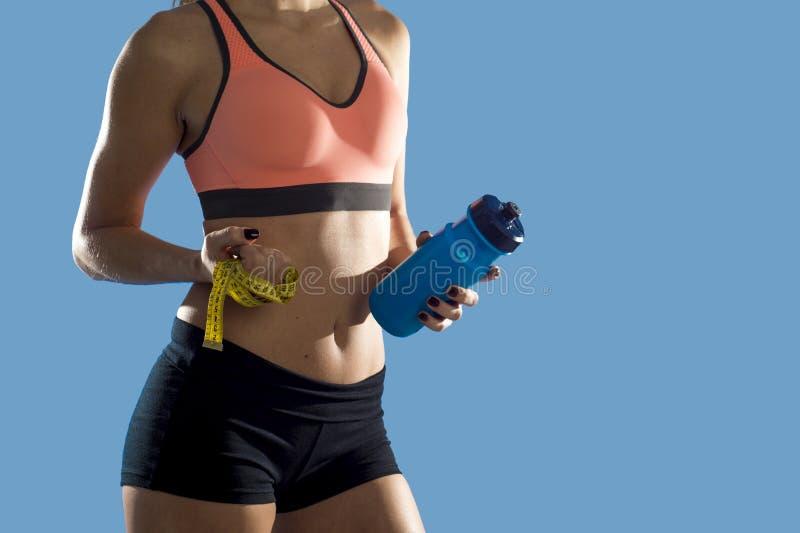 De fles van het de holdingswater van de sportvrouw en maatregelenband die slanke perfecte abs en maag tonen royalty-vrije stock foto