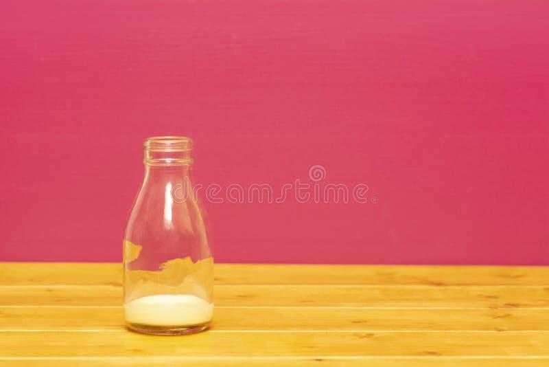 De fles van de het glasmelk van de één derdepint met residu's van banaanmilkshake royalty-vrije stock afbeeldingen
