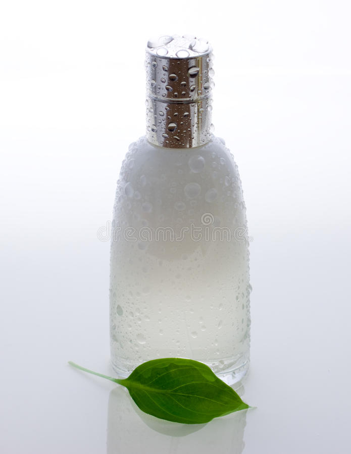 De fles van het parfum en groen blad met dalingen stock foto