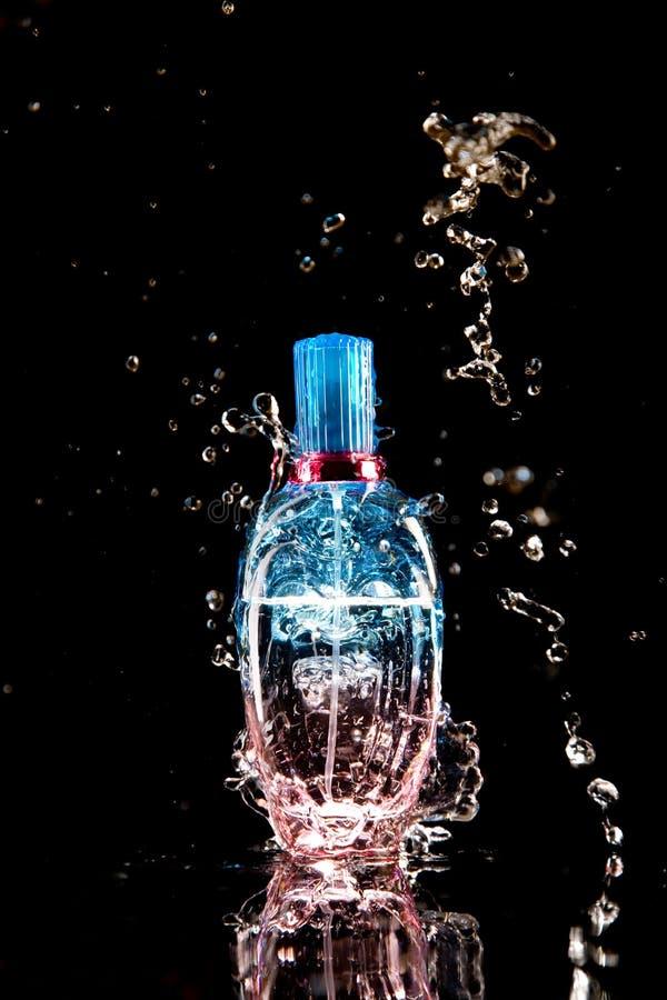 De fles van het parfum met waterplonsen stock foto's