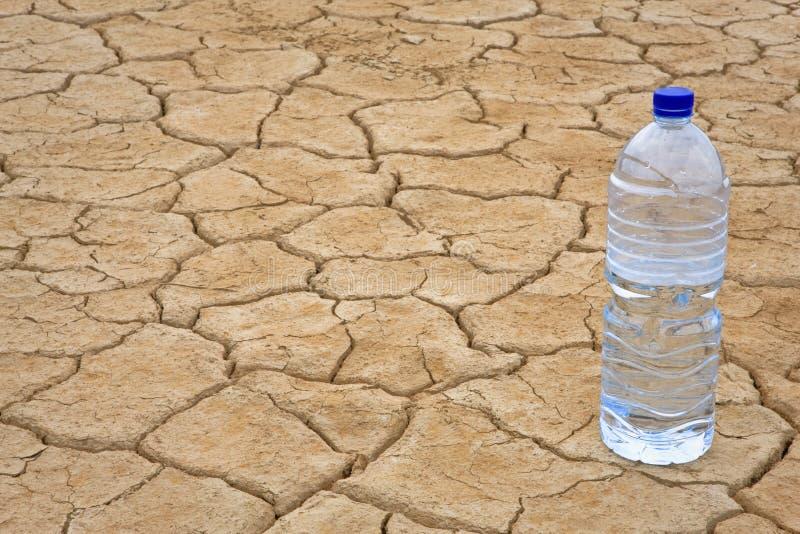 De fles van het water op droge grond royalty-vrije stock afbeeldingen