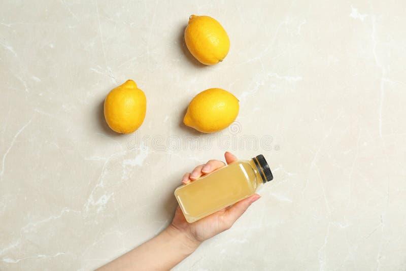 De fles van de vrouwenholding met vers sap dichtbij citroenen stock fotografie